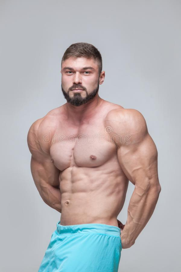 Silna Sportowa mężczyzna sprawności fizycznej modela półpostać pokazuje sześć paczek abs odizolowywający na popielatym tle z copy zdjęcia stock