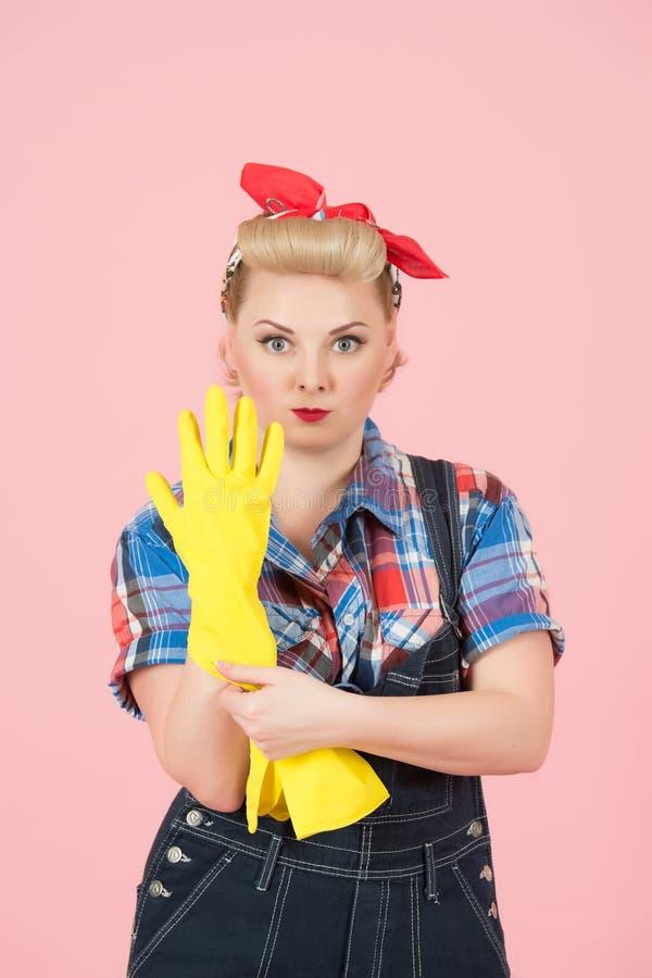 Silna szpilka projektujący blondynki dziewczyny wp8lywy na ręki gumowej żółtej rękawiczce dla czyścić Kobieta w drelichowym wp8ly zdjęcia stock