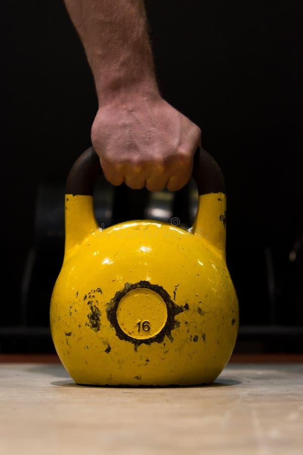Silnego mężczyzna ręki mienia stary i używać duży żółty kettlebell na drewnianej podłoga w gym obraz stock
