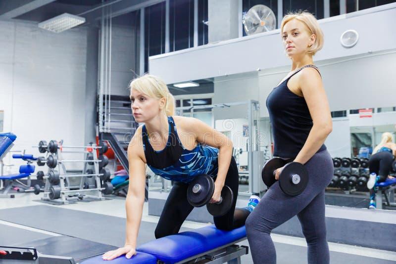 Silnej kobiety dumbbells podnośni ciężary Dysponowanej dziewczyny atrakcyjnej blondynki budynku wzorcowi ćwiczy zyskuje mięśnie p obraz stock