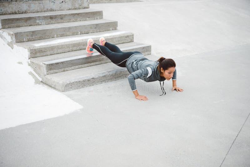 Silnej sprawności fizycznej miastowa kobieta podnosi robić pcha zdjęcie royalty free