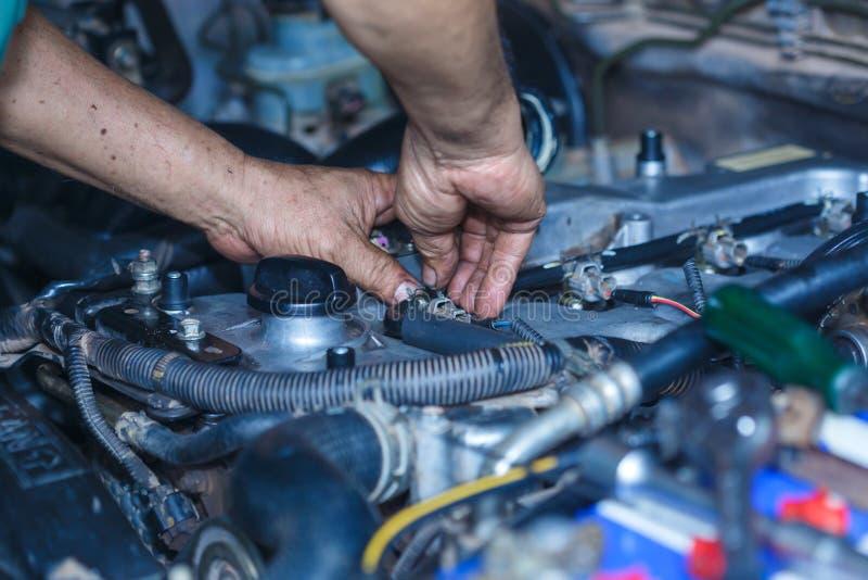 Silnik naprawa, mechanik pracuje w samochodzie pod kapiszonem obrazy royalty free