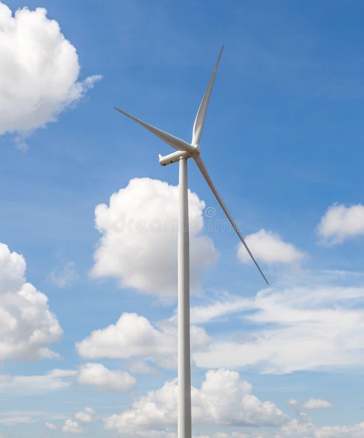 Silnik wiatrowy w pięknym chmurnym niebieskiego nieba tle, concep obraz royalty free