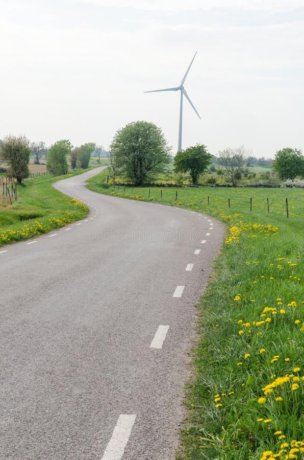 Silnik wiatrowy wijącą wiejską drogą zdjęcia royalty free