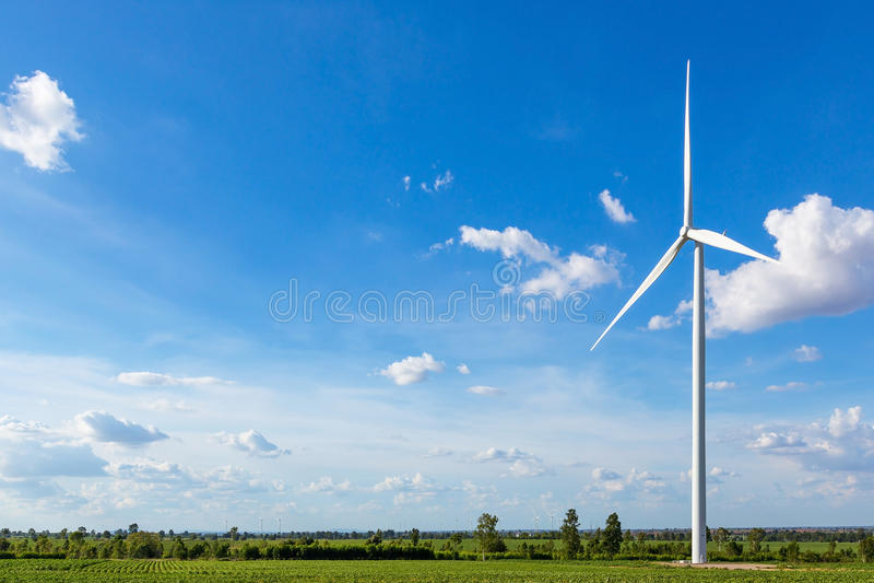 Silniki wiatrowi w polu przeciw niebieskie niebo wywołującej elektryczności obraz stock