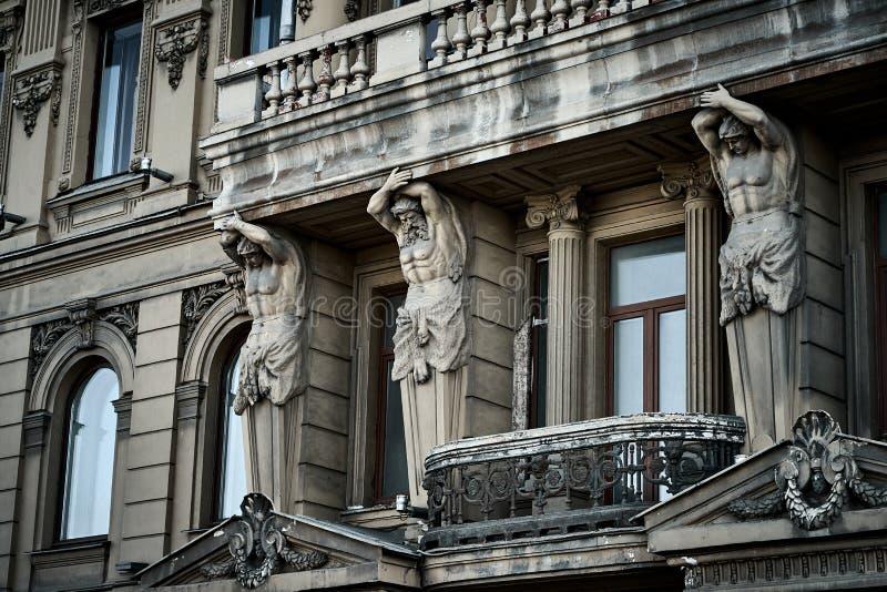 Silny Atlants jest podporowym balkonem na fasadzie dziejowy budynek w Petersburg zdjęcia royalty free