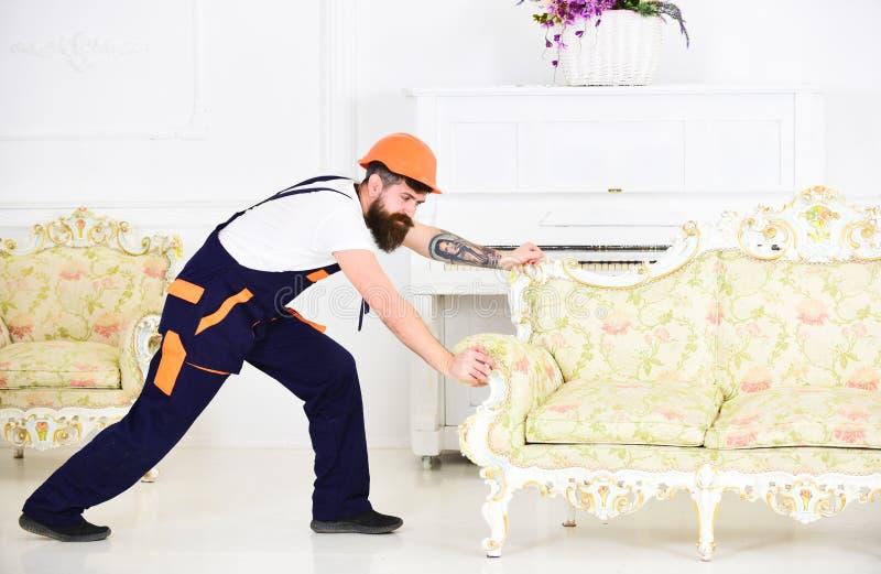 Silny brodaty facet przenosi starą piękną kanapę w niedawno przekonstruowywającym mieszkaniu Pracownik próbuje ruszać się z tatua zdjęcie stock