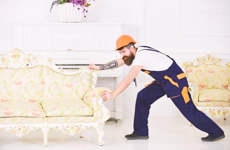 Silny brodaty facet przenosi starą piękną kanapę w niedawno przekonstruowywającym mieszkaniu Pracownik próbuje ruszać się z tatua zdjęcia royalty free