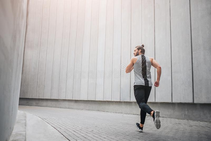 Silny i budujący biegacz jogging przez betonowego korytarza On jogging z wszystkie władzą i siłą - panie young zdjęcie stock