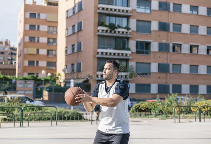 Silny koszykarz przygotowuje się do rzucenia dobrym strzałem w koszyk na środku miejskiego boiska obrazy royalty free