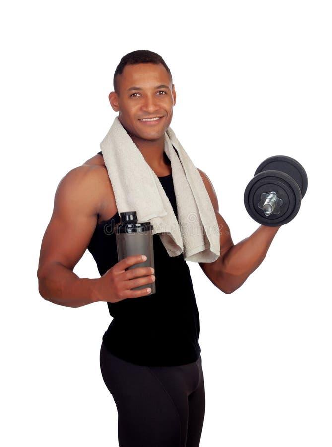Silny Latyno-amerykański mężczyzna pije proteinę póżniej z dumbbells zdjęcia royalty free
