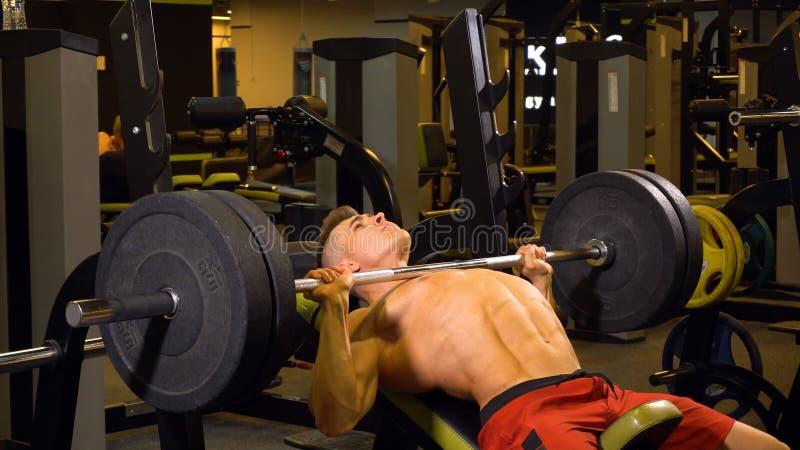 Silny mężczyzna robi ćwiczeniom z barbell w gym obrazy stock