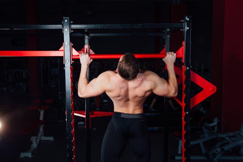 Silny mężczyzna robi ciągnieniu podnosi przystojnej atlety przy gym duży ufny mięśniowy szkolenie obrazy stock