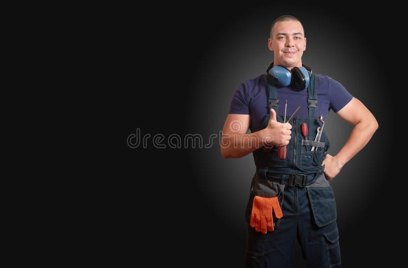 Silny męski mechanik w błękitnej overal pozycji na czarnym tle zdjęcia stock