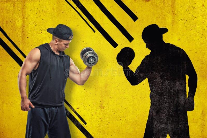 Silny mięśniowy młody człowiek w czarnym sportswear z dumbbell z czarnym cieniem na żółtym tle zdjęcia royalty free