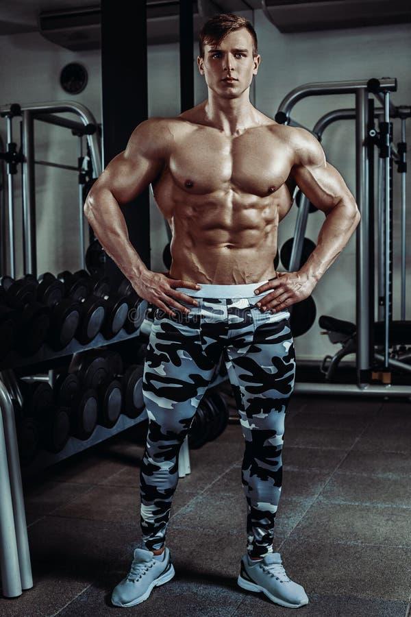Silny mięśniowy bodybuilder robi ćwiczeniu w gym Część sprawności fizycznej ciało fotografia royalty free