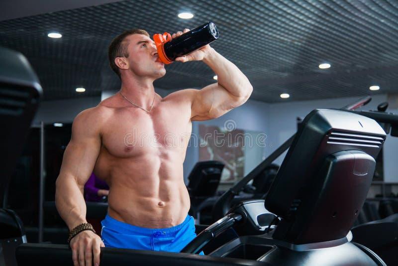 Silny mięśniowy bodybuilder robi cardio ćwiczeniu na kieratowej napój wodzie obrazy stock