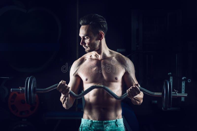 Silny Mięśniowy mężczyzna pracujący w gym robi ćwiczeniom z barbell przy bicepsami out fotografia stock