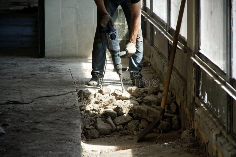 Silny mięśniowy mężczyzna rozmontowywa cementowego podłogowego poncz zdjęcia stock