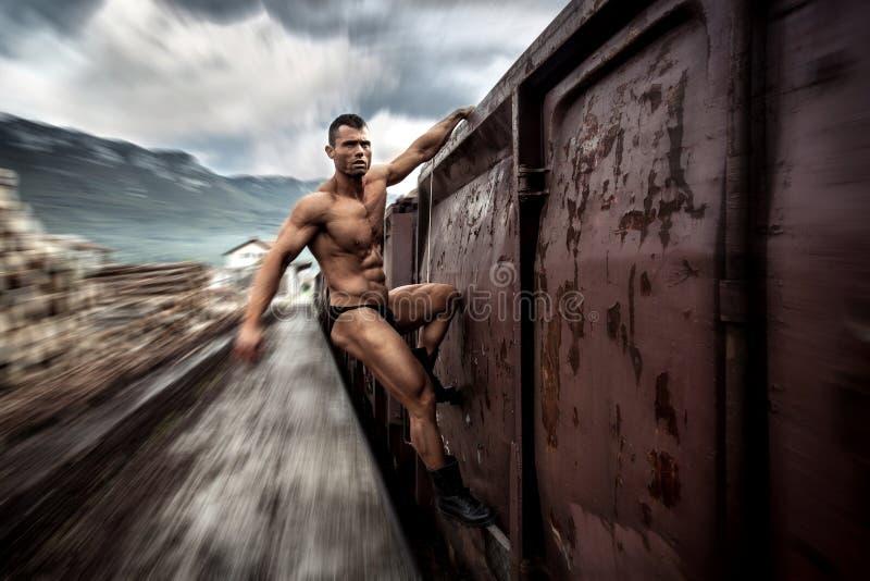 Silny mięśniowy mężczyzna trzyma dalej ruszać się pociąg zdjęcia royalty free