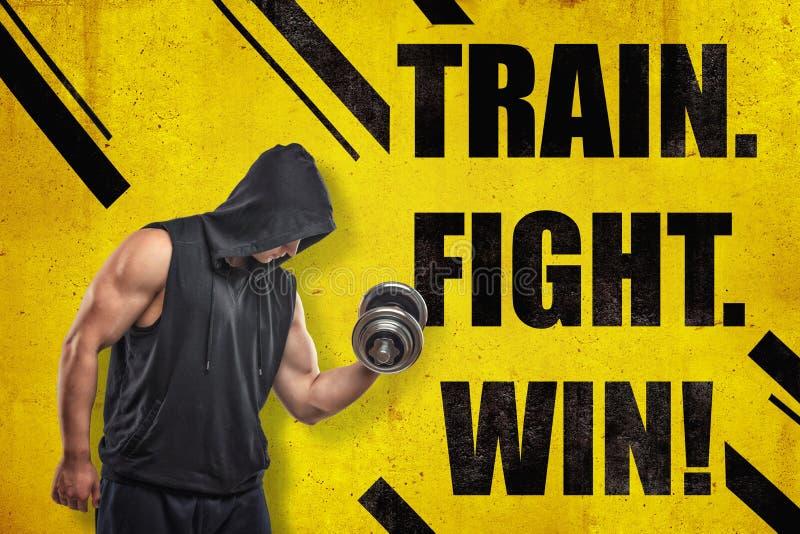 Silny mięśniowy młody człowiek w czarnym sportswear z pociągiem i dumbbell « wojownik WYGRANY «znak na żółtym tle royalty ilustracja