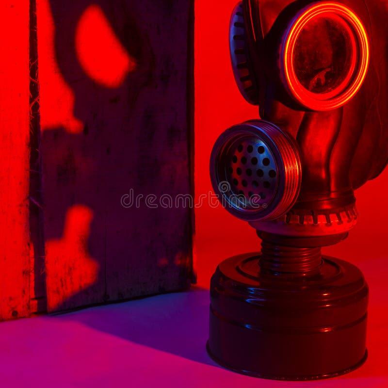 Silny poziom niebezpieczeństwo Cień maska gazowa z błoną spada na kącie drewniane deski w jaskrawym czerwonym świetle fotografia royalty free