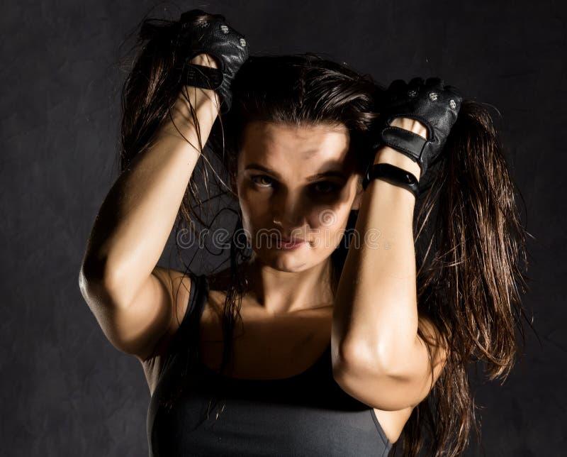 Silny seksowny żeński bokser lub mma wojownik jest ubranym czarne rękawiczki na ciemnym tle obraz stock