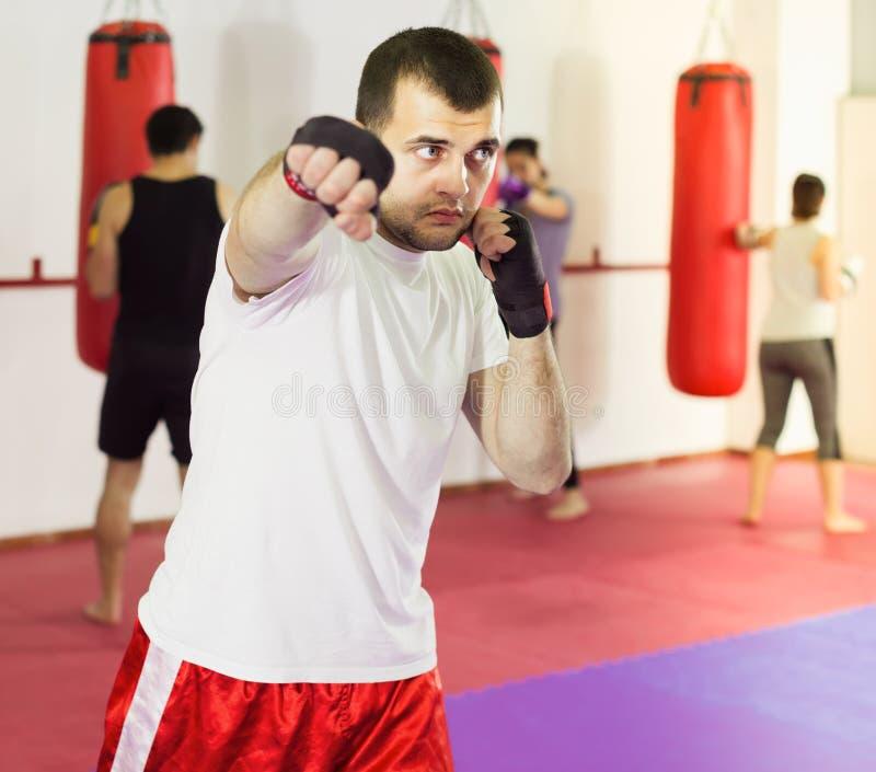 Silny sportowiec w bokserskiej sala ćwiczy boksujący poncz zdjęcia royalty free