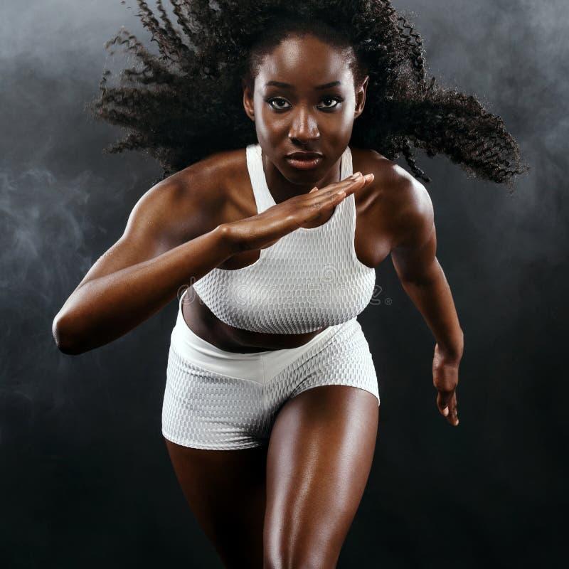 Silny sportowy czarny skóry kobiety szybkobiegacz, biega na tle z dymem jest ubranym w sportswear oblicza sprawność fizyczną kilk obraz stock