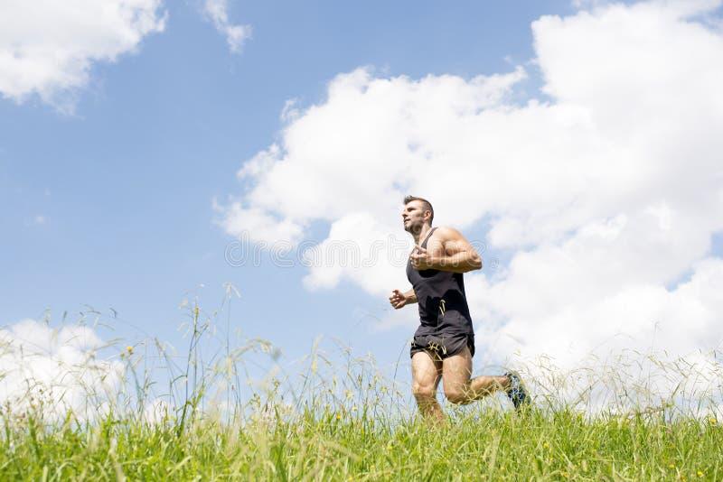 Silny sportowy mężczyzna bieg na polu zdjęcia stock