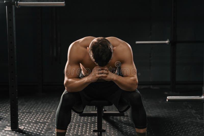 Silny sporty mężczyzny obsiadanie na gym ławki cierpienia awarii pokonywać zdjęcie royalty free