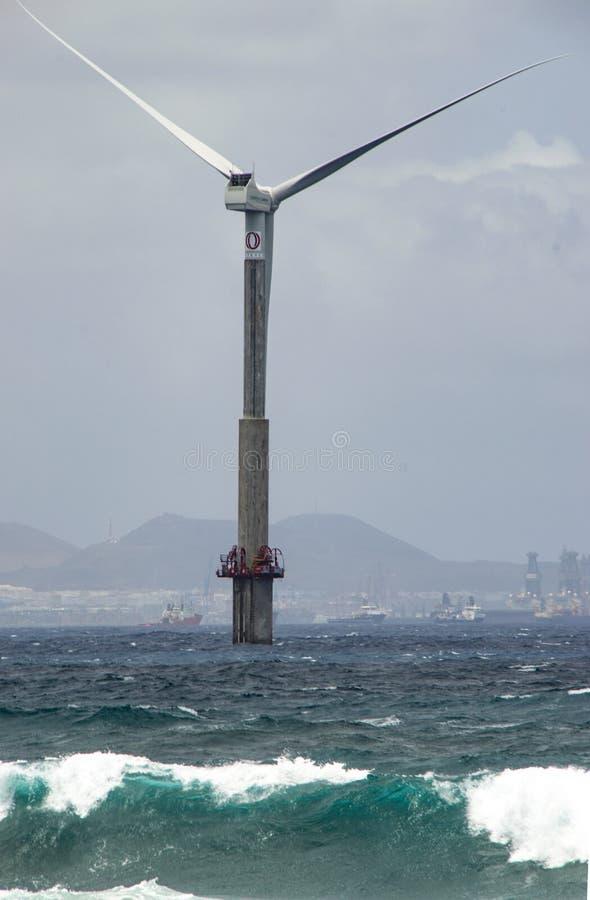 Silny wiatr turbina wierza na morzu z dużym miasta tłem i fala obraz royalty free