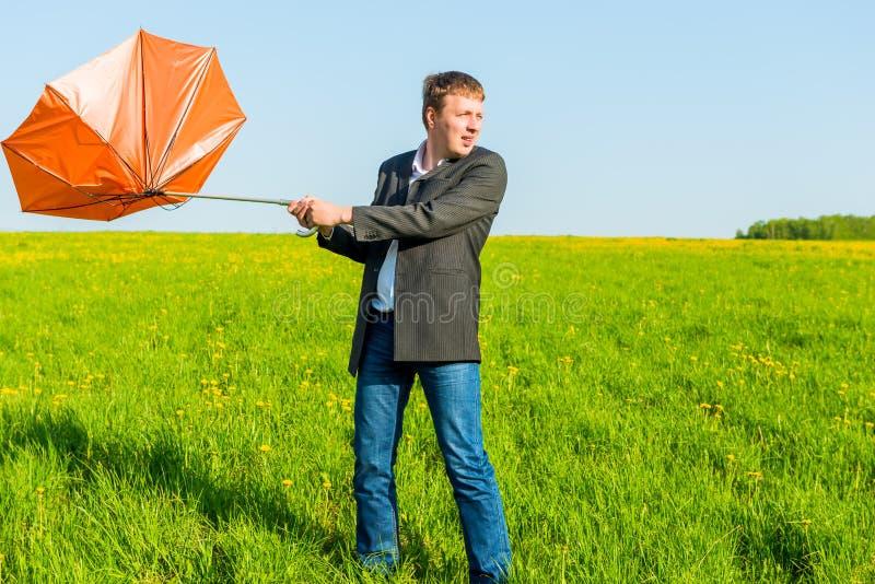 Silny wiatr wrenched parasolowy mężczyzna obrazy stock