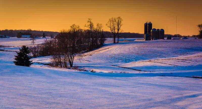 Silo's en sneeuw behandelde landbouwbedrijfgebieden bij zonsondergang in de landelijke Telling van York royalty-vrije stock afbeelding
