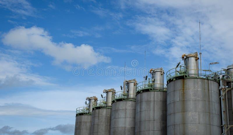 Silo's in petrochemische installaties met blauwe lucht stock foto's