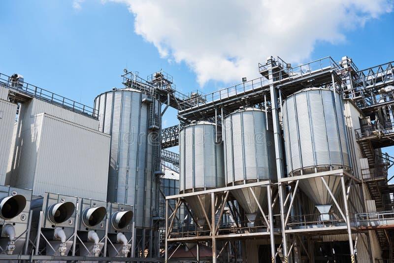 Silos agrícolas Exterior constructivo Almacenamiento y sequedad de granos, trigo, maíz, soja, girasol contra el cielo azul fotos de archivo libres de regalías