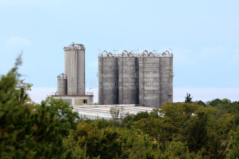 Silos concrets grands de stockage au-dessus du complexe industriel entouré avec la végétation forestière et la mer denses avec le images stock
