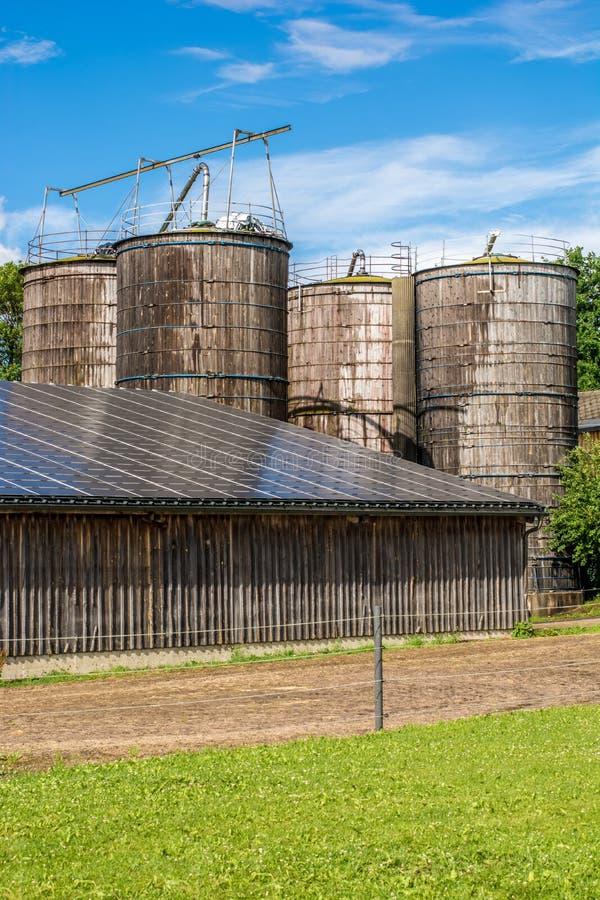 Silos de grano y silos de la alimentación en una granja vieja con el sistema fotovoltaico moderno en un granero imagen de archivo libre de regalías