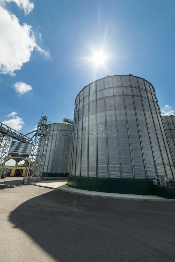 Silos del alto metal para el almacenamiento del trigo y de la cebada Día soleado, el cielo azul fotos de archivo