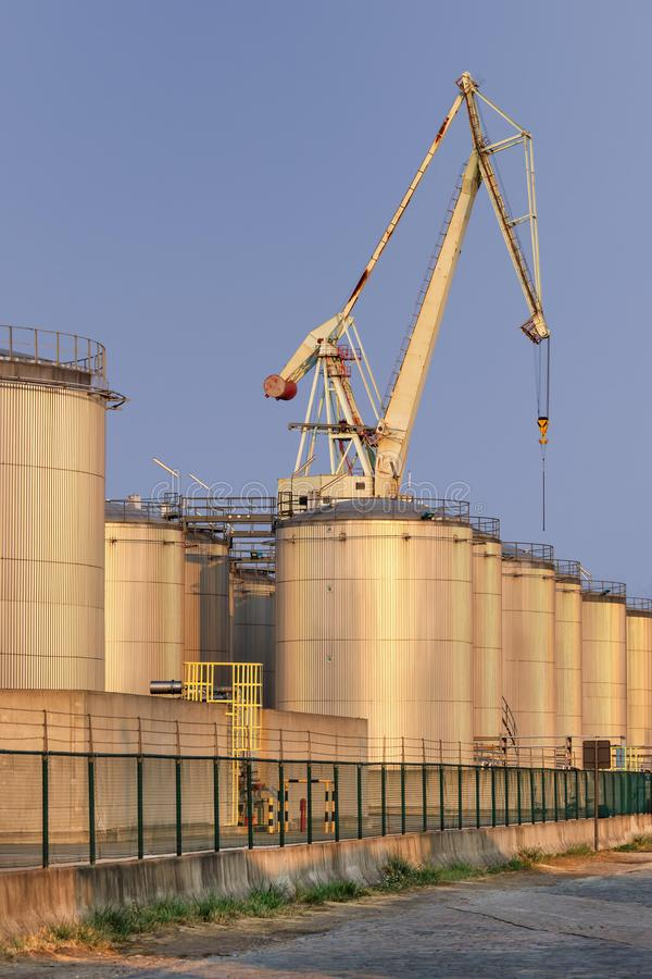 Silos at an oil refinery in late afternoon, Port of Antwerp, Belgium. Silos at an oil refinery with warm light in late afternoon, Port of Antwerp, Belgium stock image
