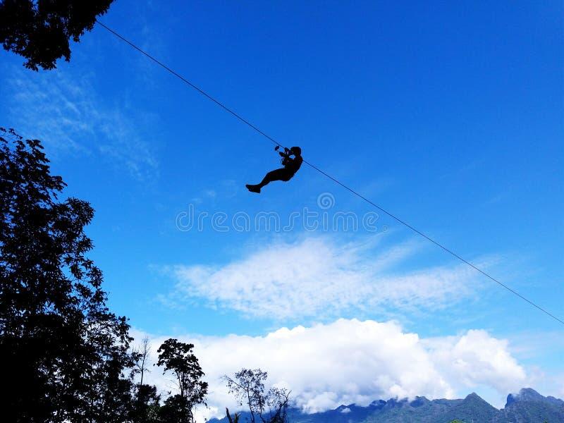 Silouette人或妇女吊索和飞行在天空与云彩、山和树 免版税库存图片