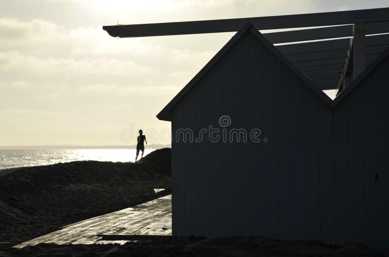Silouette di un ragazzo che salta dalla duna davanti al mare brillantemente acceso fotografie stock
