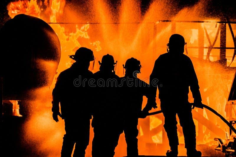 Silouhette dei pompieri che tengono la linea fotografie stock