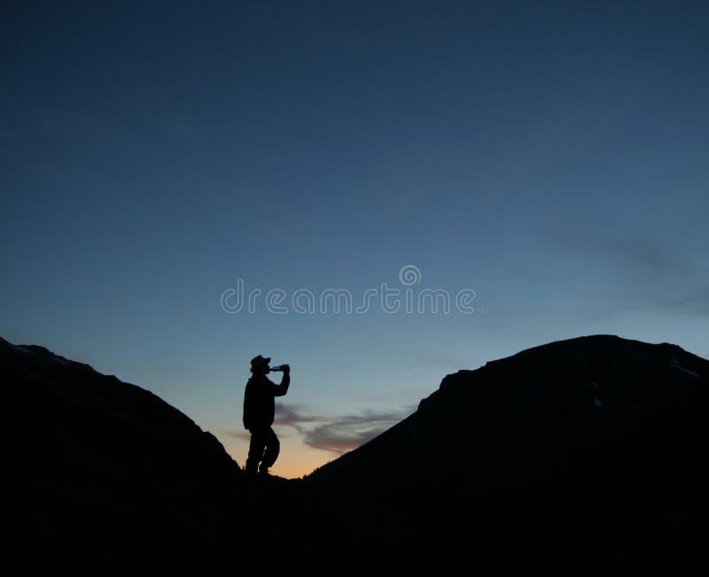Silouhette Do Caminhante Que Bebe Do Frasco Nas Montanhas Imagens de Stock Royalty Free