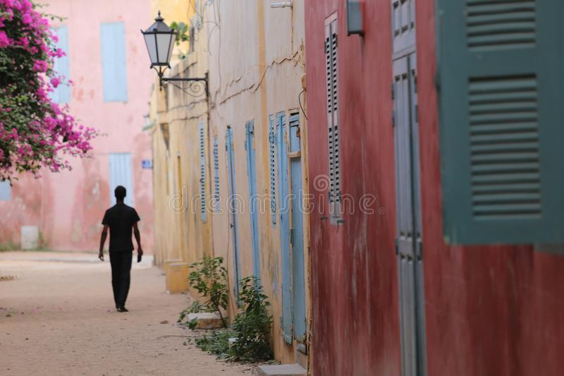 Silouhette in a small street of Goree in Senegal. A man is walking alone in a small street of Goree in Senegal. All the old houses are painted in pink or yellow royalty free stock images