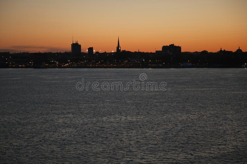 Cityscape of Trois-Rivières, Québec, Canada at sunset. Silouhetted cityscape of Trois-Rivières, Québec, Canada, with church steeple by the river at royalty free stock image