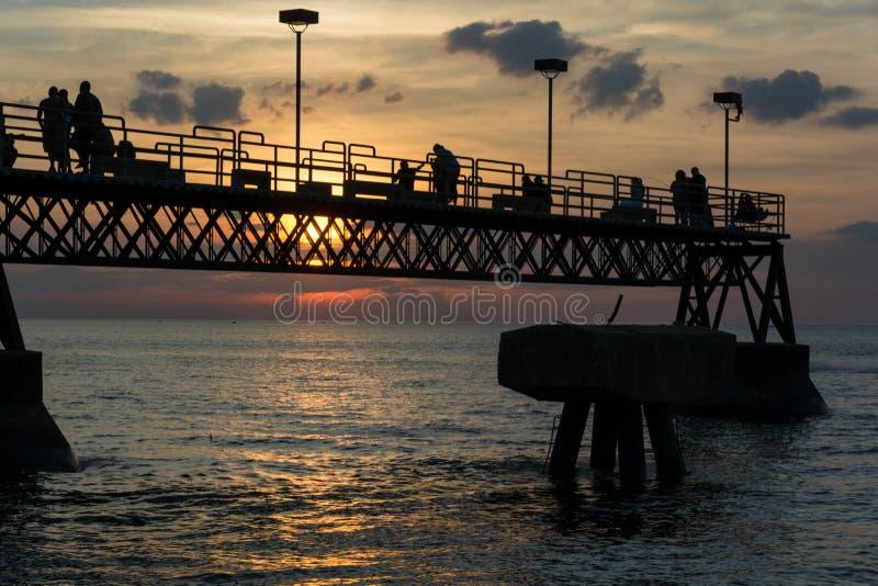 Siloutte av folk på att fiska Pier Lake Erie arkivfoton