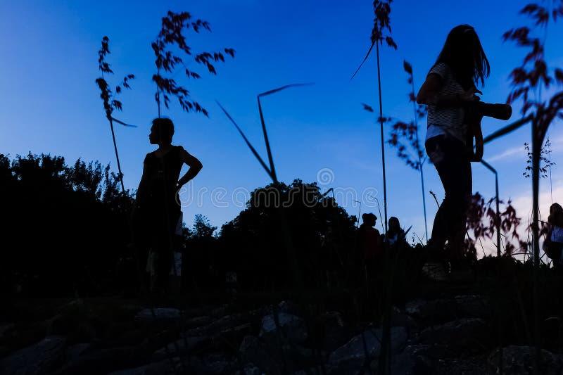 Siluate观点的放松在水坝的日落的人 免版税图库摄影