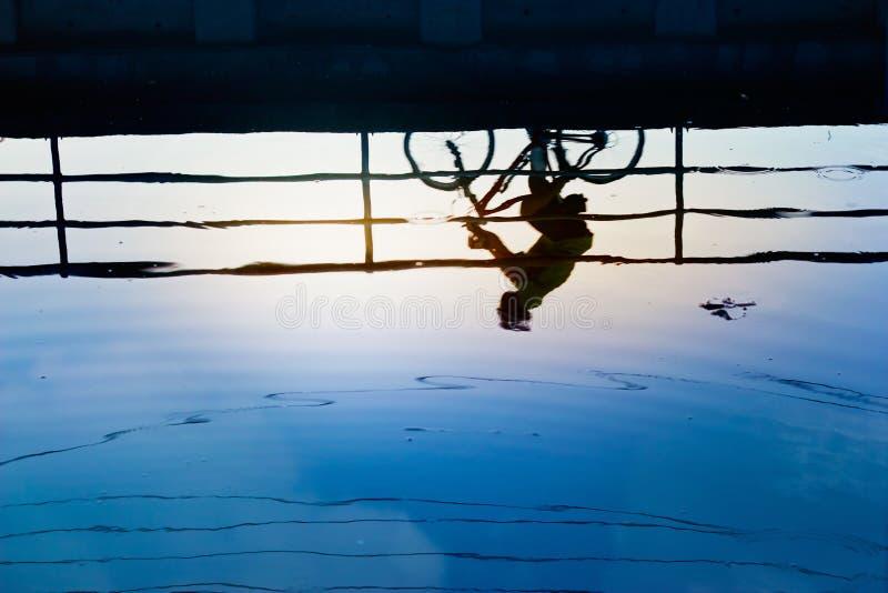 Siluate e reflexão do homem da bicicleta na água fotos de stock