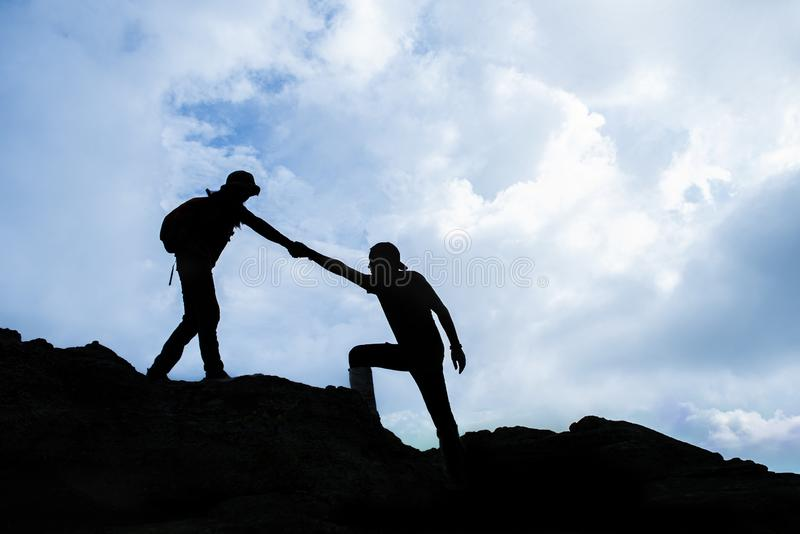 Siluate of Woman helping to pull friend from cliff. Thailand stock image